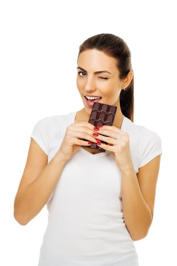 Η όμορφη νέα ευτυχής γυναίκα brunette στην άσπρη μπλούζα κρατά τη σοκολάτα και την δαγκώνει, κλείσιμο του ματιού Στην άσπρη ανασκ στοκ φωτογραφία με δικαίωμα ελεύθερης χρήσης