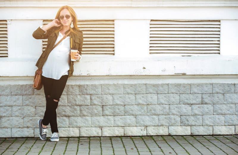 Η όμορφη νέα κατανάλωση εγκύων γυναικών παίρνει μαζί τον καφέ στοκ φωτογραφία με δικαίωμα ελεύθερης χρήσης