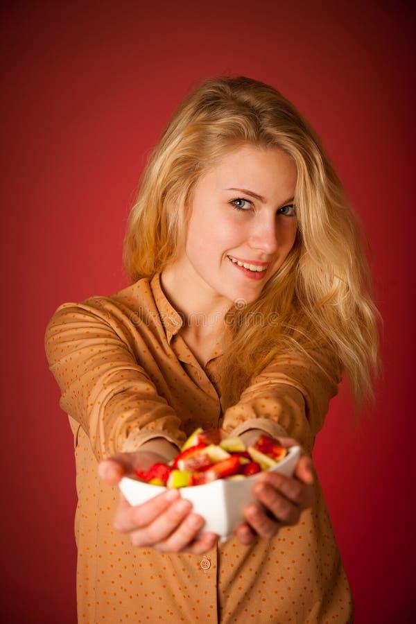 Η όμορφη νέα καυκάσια ξανθή γυναίκα κρατά εύγευστα φρούτα s στοκ φωτογραφίες με δικαίωμα ελεύθερης χρήσης