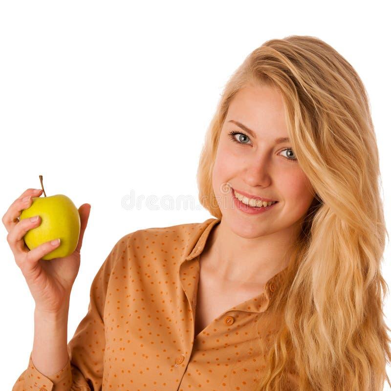 Η όμορφη νέα καυκάσια ξανθή γυναίκα τρώει ένα πράσινο μήλο ως s στοκ εικόνες
