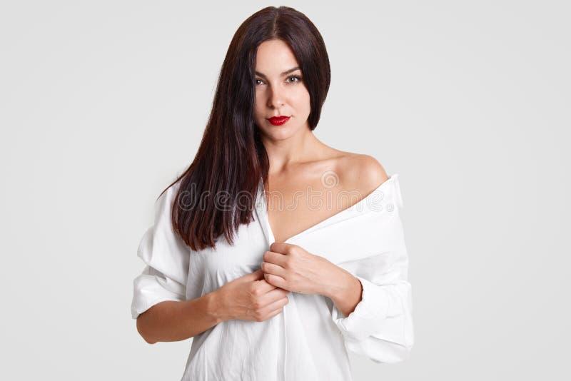 Η όμορφη νέα κυρία με το τέλειο καθαρό δέρμα, έχει το κόκκινο κραγιόν, φορά το χαλαρό άσπρο πουκάμισο, παρουσιάζει γυμνό ώμο, φλε στοκ φωτογραφίες