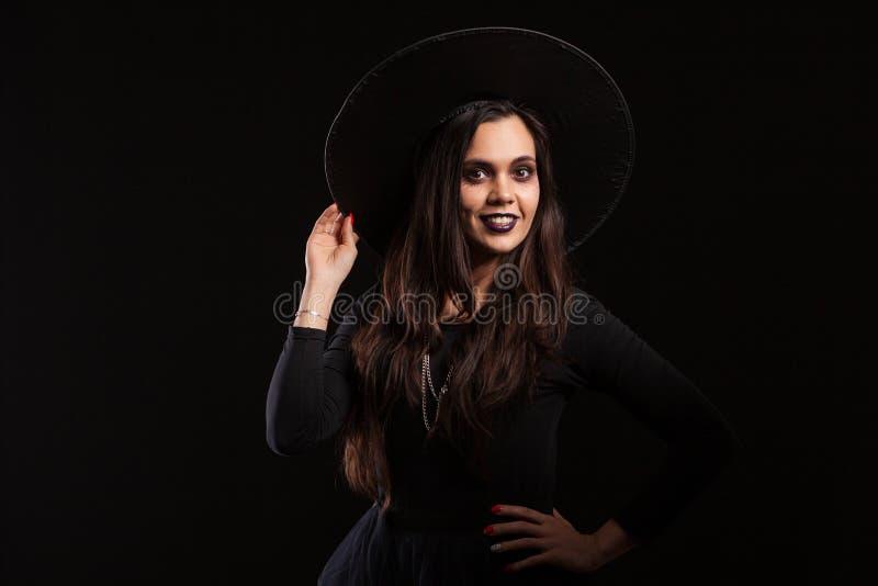 Η όμορφη νέα μάγισσα brunette που κρατά το καπέλο της με την παραδίδει το μαύρο υπόβαθρο στοκ φωτογραφίες με δικαίωμα ελεύθερης χρήσης