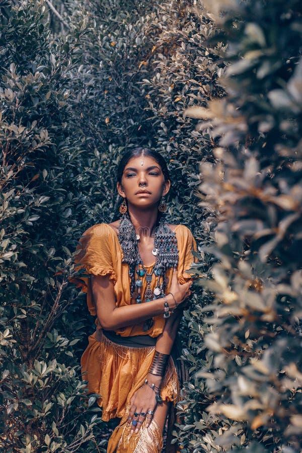 Η όμορφη νέα μοντέρνη γυναίκα με κάνει τα επάνω και μοντέρνα εξαρτήματα boho θέτοντας στο φυσικό τροπικό υπόβαθρο στοκ εικόνα