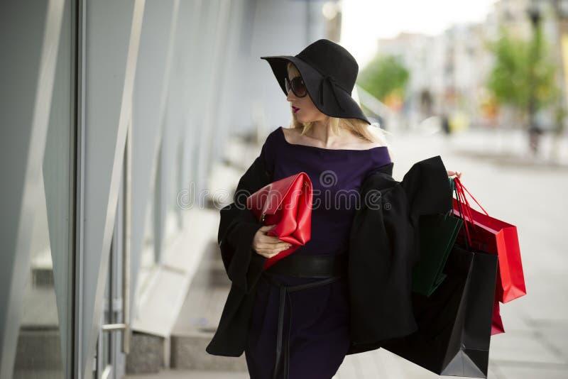 Η όμορφη νέα μοντέρνη ξανθή γυναίκα στο μπλε φόρεμα, το παλτό, τα γυαλιά ηλίου και το καπέλο με τις αγορές τοποθετεί το περπάτημα στοκ εικόνα