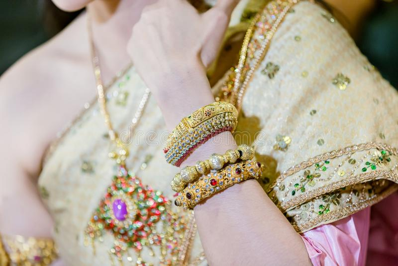 η όμορφη νέα νύφη βάζει τα χέρια στα χρυσά βραχιόλια ένδυσης περιτυλίξεων στον καρπό και το δαχτυλίδι γαμήλιων διαμαντιών της, στοκ εικόνα