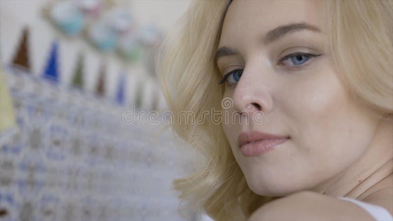Η όμορφη νέα ξανθή γυναίκα με τα μπλε μάτια φαίνεται γοητευτική και χαμογελά r Νέα γυναίκα που εξετάζει και που χαμογελά τη κάμερ στοκ εικόνα με δικαίωμα ελεύθερης χρήσης