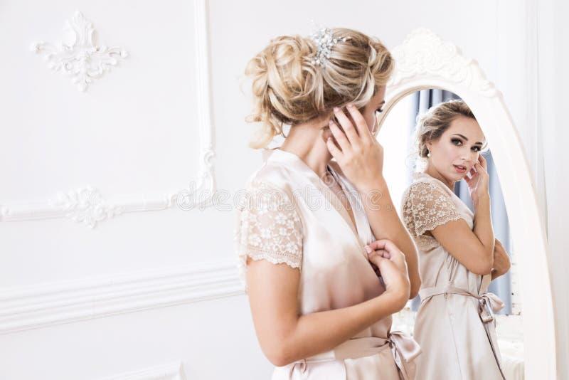 Η όμορφη νέα προκλητική ξανθή γυναίκα σε μια τήβεννο μεταξιού στέκεται μπροστά από τον καθρέφτη στοκ εικόνες