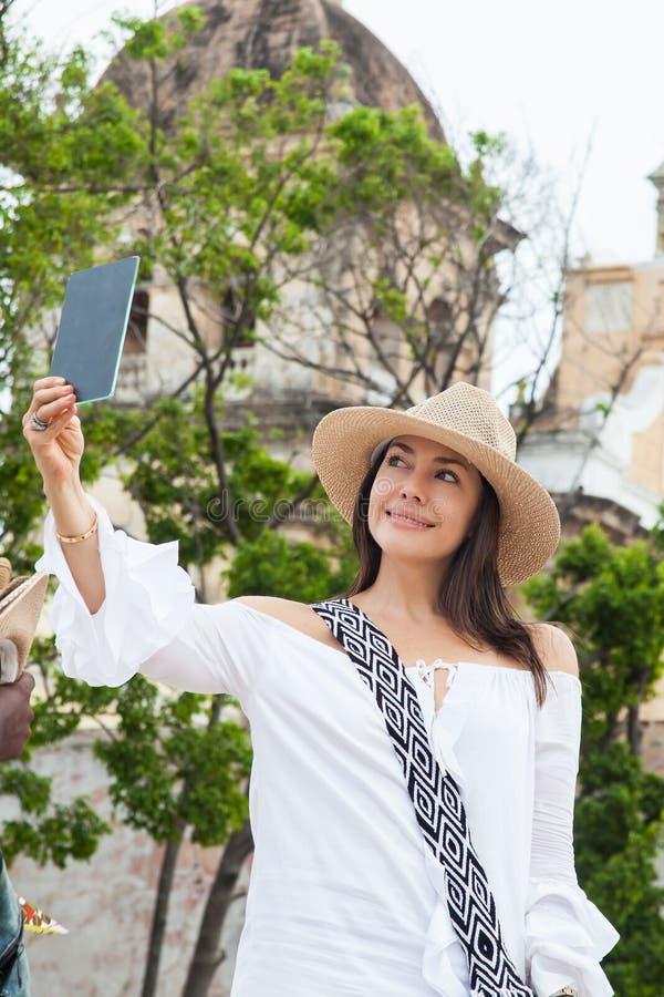 Η όμορφη νέα προσπάθεια γυναικών στα καπέλα να αγοράσουν ένα από έναν πλανόδιο πωλητή στην Καρχηδόνα de Indias περιτοίχισε την πό στοκ φωτογραφίες με δικαίωμα ελεύθερης χρήσης