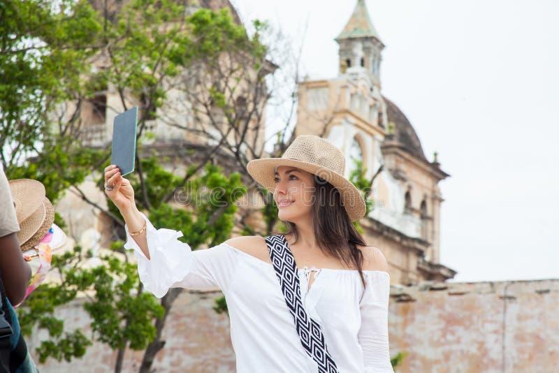 Η όμορφη νέα προσπάθεια γυναικών στα καπέλα να αγοράσουν ένα από έναν πλανόδιο πωλητή στην Καρχηδόνα de Indias περιτοίχισε την πό στοκ εικόνες