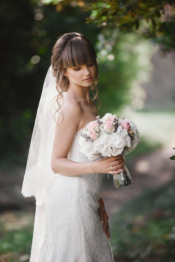 Η όμορφη νέα χαμογελώντας νύφη κρατά τη μεγάλη γαμήλια ανθοδέσμη με τα ρόδινα τριαντάφυλλα Γάμος στους ροδοειδείς και πράσινους τ στοκ φωτογραφίες με δικαίωμα ελεύθερης χρήσης