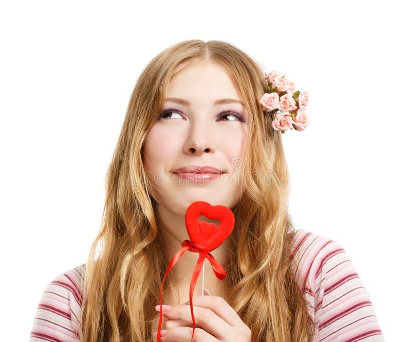 Η όμορφη νέα χαμογελώντας γυναίκα σε στοχαστικό θέτει με κόκκινο valent στοκ εικόνα με δικαίωμα ελεύθερης χρήσης