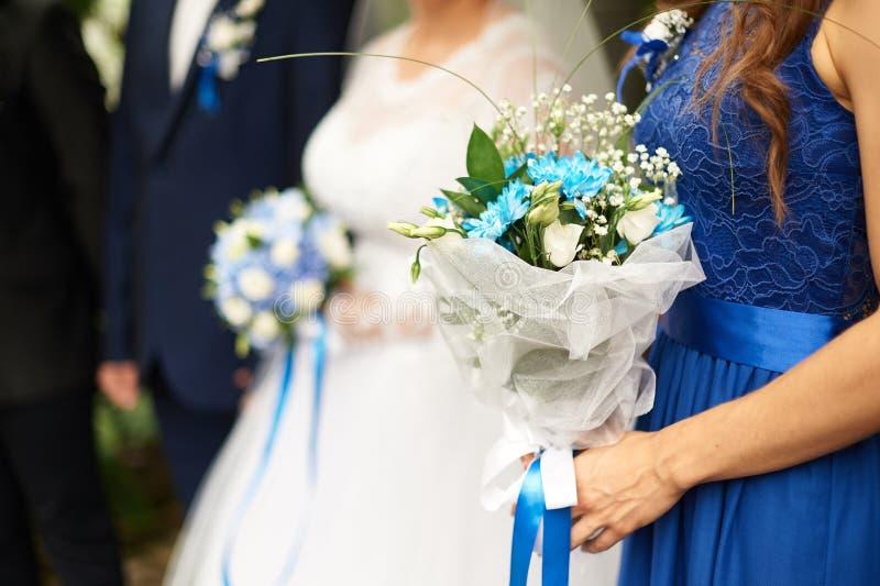 Η όμορφη νυφική ανθοδέσμη των τριαντάφυλλων και τα hydrangeas στη νύφη και το νεόνυμφο υποβάθρου στέκονται σε μια γαμήλια τελετή στοκ φωτογραφία