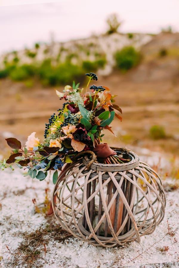 Η όμορφη νυφική ανθοδέσμη σε μια ξύλινη στάση υπαίθρια Γαμήλια floristic διακόσμηση στοκ εικόνες