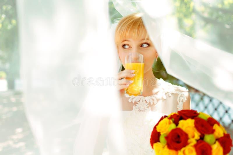 Η όμορφη νύφη πίνει το χυμό από πορτοκάλι που στέκεται κάτω από ένα πέπλο στοκ εικόνα με δικαίωμα ελεύθερης χρήσης