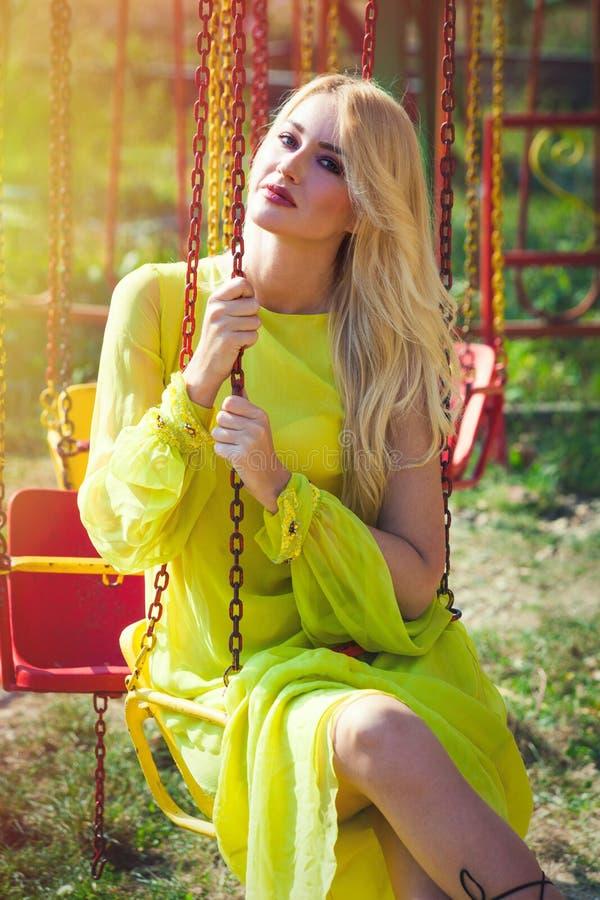 Η όμορφη ξανθή γυναίκα μόδας στο μακρύ κομψό κίτρινο φόρεμα κάθεται στο πετώντας ιπποδρόμιο το καλοκαίρι λούνα παρκ στοκ εικόνες