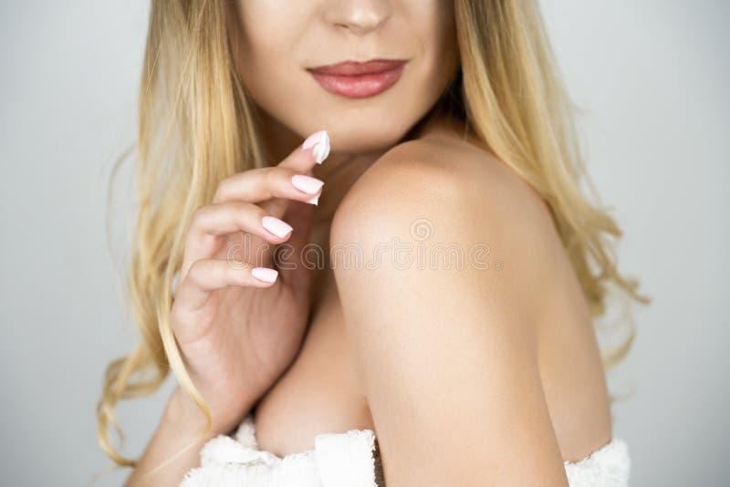 Η όμορφη ξανθή γυναίκα που εφαρμόζει την κρέμα ομορφιάς σε την ώμος κοντά επάνω απομόνωσε το άσπρο υπόβαθρο στοκ φωτογραφίες με δικαίωμα ελεύθερης χρήσης