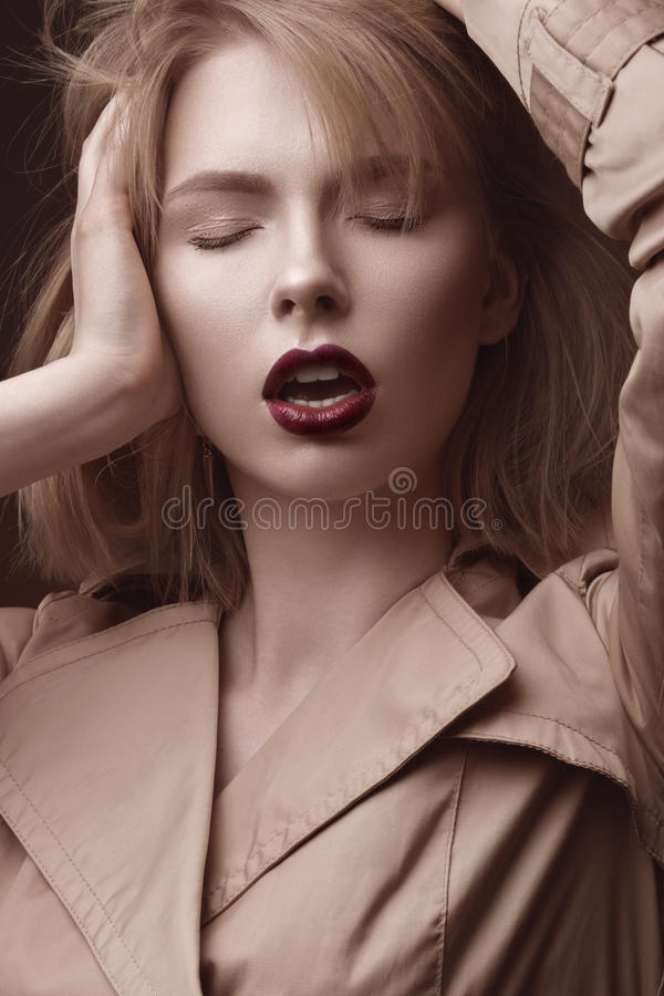 Η όμορφη ξανθή γυναίκα σε ένα φωτεινό παλτό και σκοτεινά χείλια, παρουσίαση διαφορετική θέτει Πρόσωπο ομορφιάς στοκ φωτογραφίες