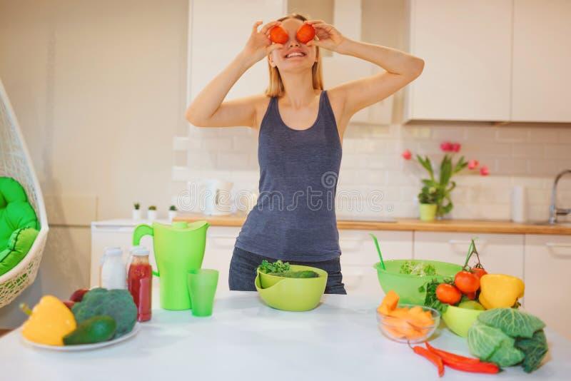 Η όμορφη ξανθή γυναίκα Vegan έχει τη διασκέδαση με τις οργανικές ντομάτες μαγειρεύοντας τα ακατέργαστα λαχανικά στην κουζίνα ακατ στοκ φωτογραφίες με δικαίωμα ελεύθερης χρήσης
