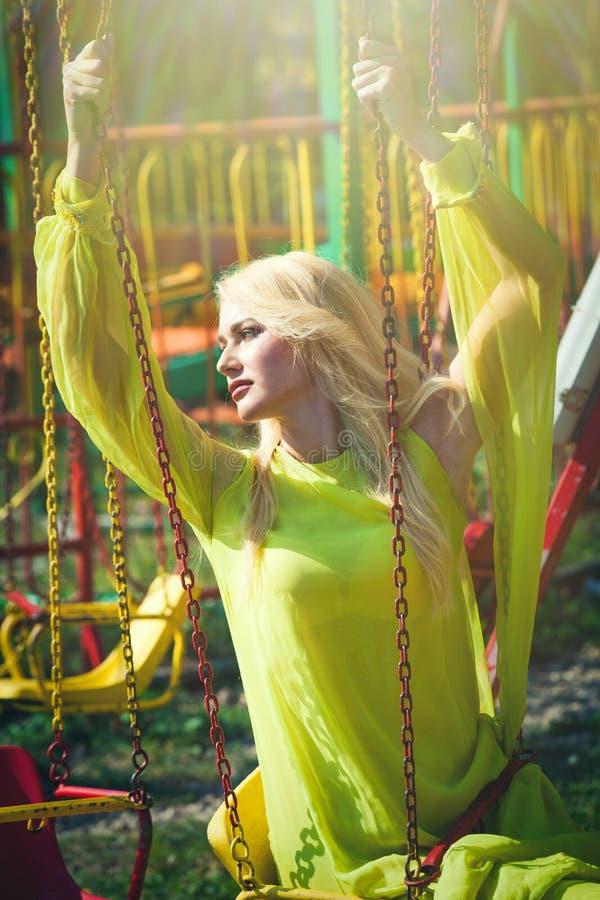 Η όμορφη ξανθή κομψή γυναίκα μόδας στο λούνα παρκ κάθεται στο πετώντας ιπποδρόμιο το μακρύ κίτρινο καλοκαίρι φορεμάτων στοκ φωτογραφία με δικαίωμα ελεύθερης χρήσης