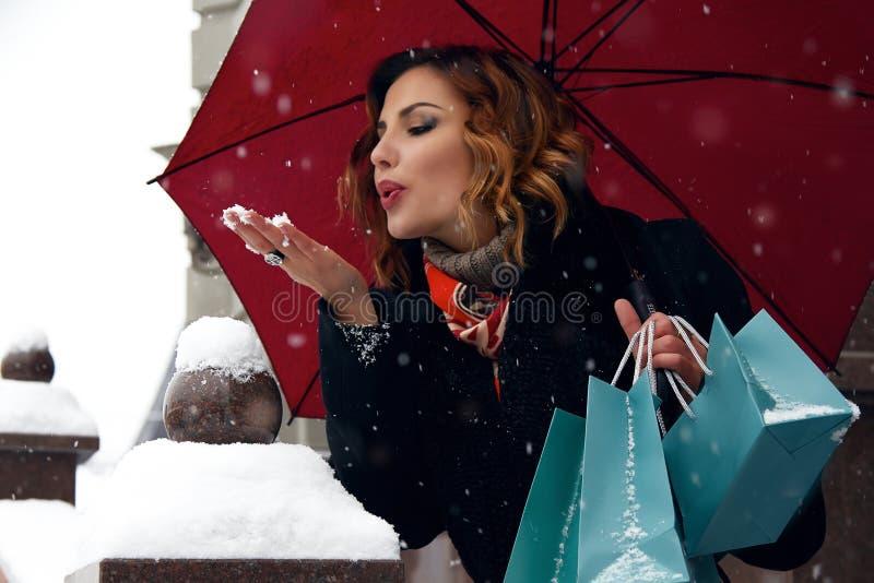 Η όμορφη οδός χιονιού γυναικών αγοράζει παρουσιάζει το νέο έτος Χριστουγέννων στοκ εικόνα