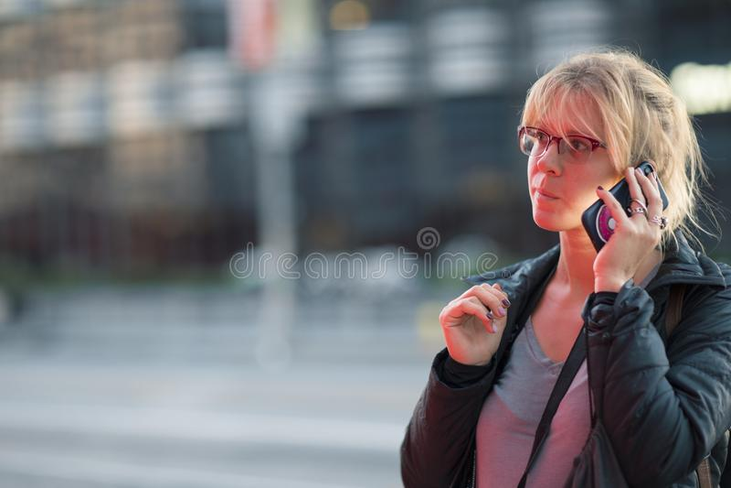 Η όμορφη ομιλία κοριτσιών στο τηλέφωνο τη νύχτα σε μια πολυάσχολη οδό πόλεων που κοιτάζει και κουράζει στοκ εικόνα με δικαίωμα ελεύθερης χρήσης