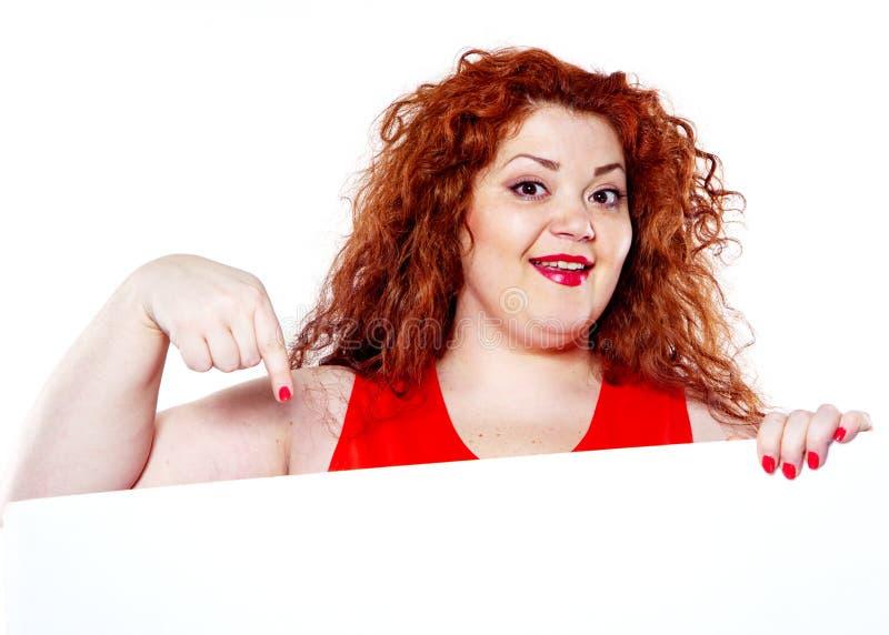 η όμορφη παχιά, μεγάλη γυναίκα αισθησιασμού με το κόκκινο κραγιόν και με τις κόκκινες μπλούζες που κρατούν το άσπρο bilboard στοκ εικόνα