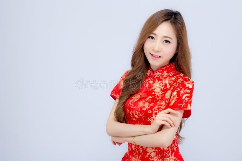 Η όμορφη πορτρέτου ευτυχής κινεζική νέα ένδυση γυναικών έτους νέα ασιατική cheongsam χαμογελά με τα συγχαρητήρια και το χαιρετισμ στοκ εικόνες