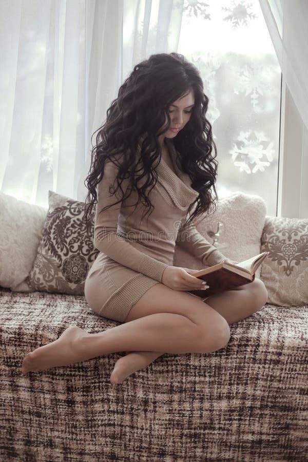 Η όμορφη προκλητική γυναίκα brunette που φορά το πλεκτό φόρεμα διάβασε το boo στοκ φωτογραφία με δικαίωμα ελεύθερης χρήσης