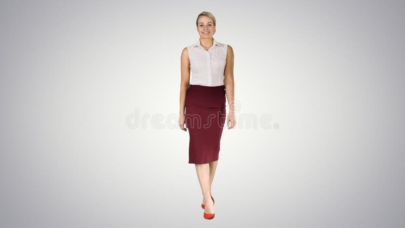 Η όμορφη προκλητική μόδα ύφους επιχειρησιακών γραφείων γυναικών brunette ντύνει το περπάτημα και το χαμόγελο στη κάμερα στην κλίσ στοκ εικόνα
