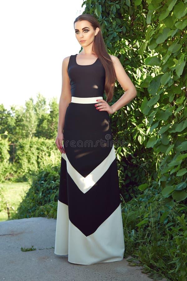 Η όμορφη προκλητική γυναίκα που φορά τον ήλιο πάρκων περιπάτων φορεμάτων λάμπει makeup στοκ εικόνα με δικαίωμα ελεύθερης χρήσης