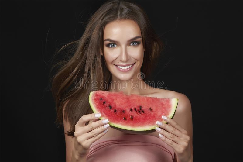 Η όμορφη προκλητική γυναίκα brunette που τρώει το καρπούζι σε ένα άσπρο υπόβαθρο, υγιή τρόφιμα, νόστιμα τρόφιμα, οργανική διατροφ στοκ φωτογραφία
