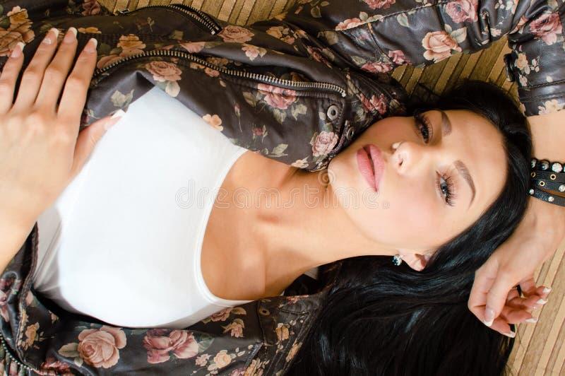 Η όμορφη προκλητική νέα γυναίκα brunette με μακρυμάλλη στο λουλούδι τύπωσε το σακάκι δέρματος που έχει τη διασκέδαση εξετάζοντας  στοκ εικόνες