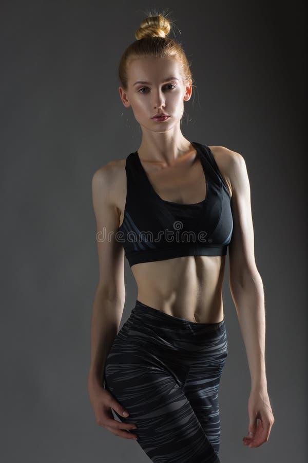 Η όμορφη προκλητική ξανθή γυναίκα που ο τέλειος αθλητικός λεπτός αριθμός που συμμετέχεται στη γιόγκα, την άσκηση ή την ικανότητα, στοκ εικόνα