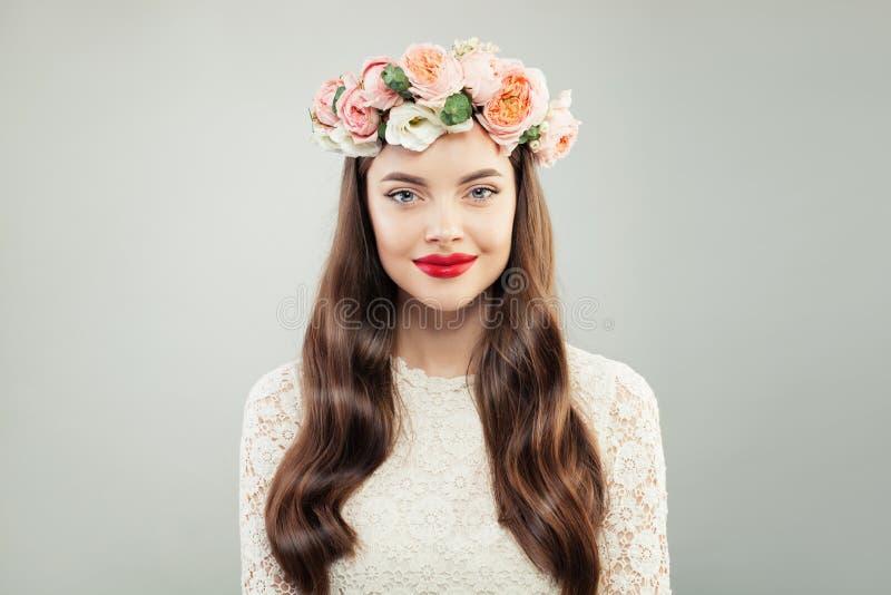 Η όμορφη πρότυπη γυναίκα με μακρυμάλλη, αποτελεί και θερινά λουλούδια Κορίτσι ομορφιάς άνοιξη, χείλια Makeup RES στοκ εικόνα