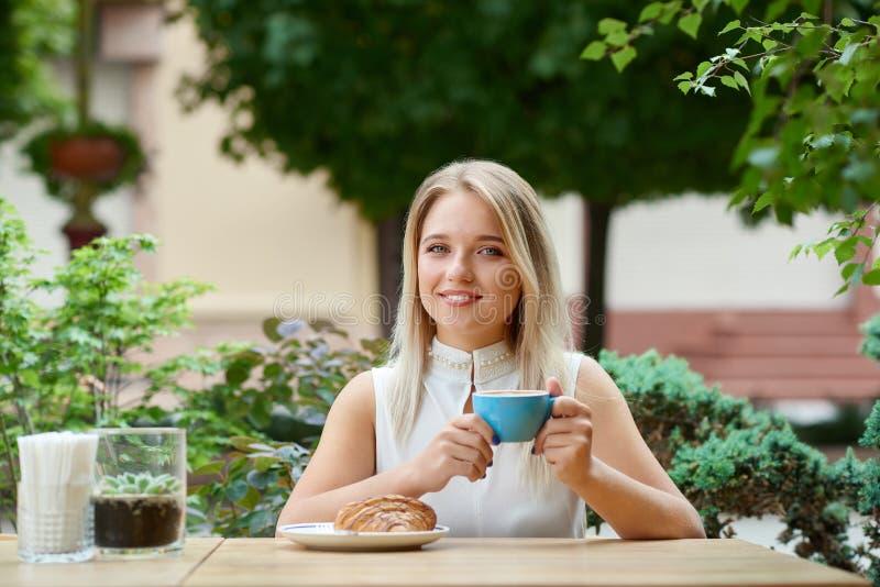 Η όμορφη συνεδρίαση κοριτσιών υπαίθρια στον καφέ κατοικεί τον καφέ κατανάλωσης, κατανάλωση croissant στοκ εικόνες με δικαίωμα ελεύθερης χρήσης