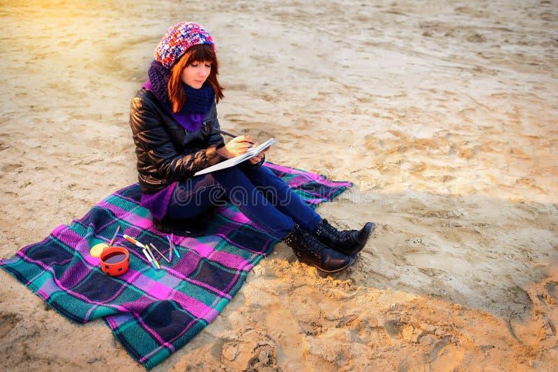 Η όμορφη συνεδρίαση κοριτσιών στην παραλία και έχει τα αρχεία σε ένα noteboo στοκ εικόνα