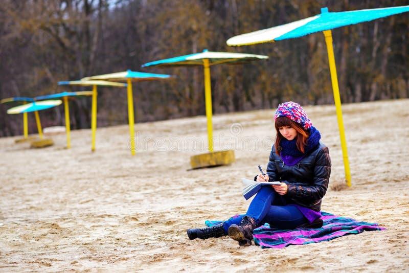 Η όμορφη συνεδρίαση κοριτσιών στην παραλία και έχει τα αρχεία σε ένα noteboo στοκ εικόνες
