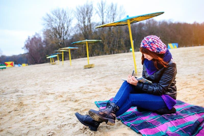 Η όμορφη συνεδρίαση κοριτσιών στην παραλία και έχει τα αρχεία σε ένα noteboo στοκ φωτογραφίες με δικαίωμα ελεύθερης χρήσης