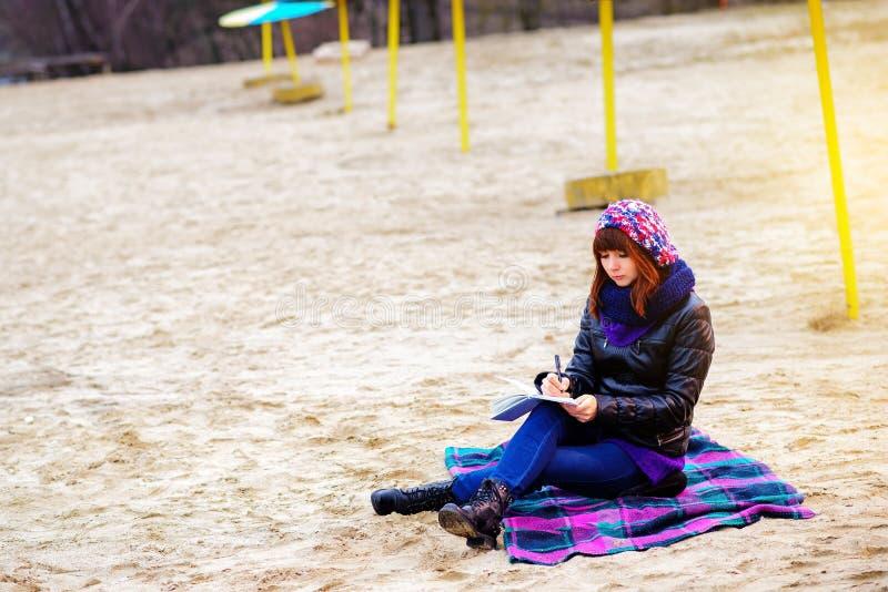 Η όμορφη συνεδρίαση κοριτσιών στην παραλία και έχει τα αρχεία σε ένα noteboo στοκ φωτογραφία