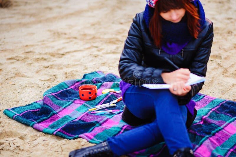 Η όμορφη συνεδρίαση κοριτσιών στην παραλία και έχει τα αρχεία σε ένα noteboo στοκ εικόνα με δικαίωμα ελεύθερης χρήσης