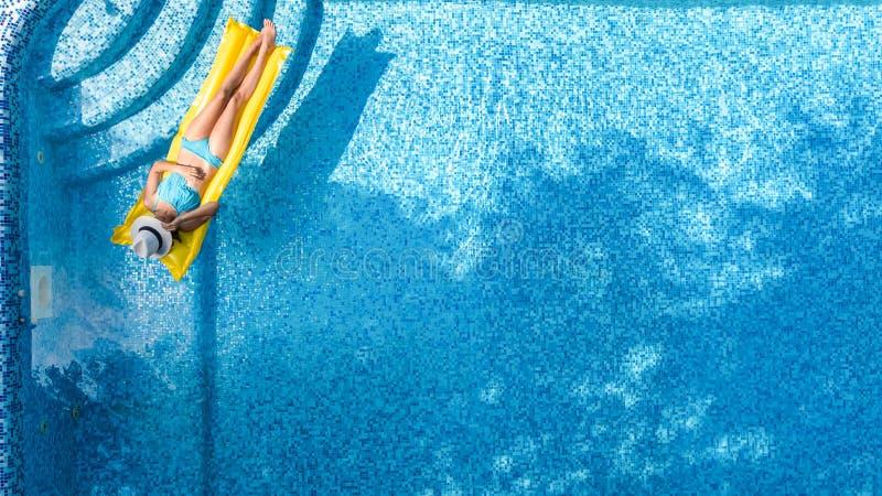 Η όμορφη χαλάρωση νέων κοριτσιών στην πισίνα, κολυμπά στο διογκώσιμο στρώμα και έχει τη διασκέδαση στο νερό στις οικογενειακές δι στοκ εικόνα