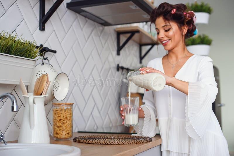 Η όμορφη χαμογελώντας γυναίκα χύνει το φρέσκο γάλα από μια καράφα σε ένα ποτήρι, στη μοντέρνη άνετη κουζίνα στο πρωί : στοκ φωτογραφία με δικαίωμα ελεύθερης χρήσης