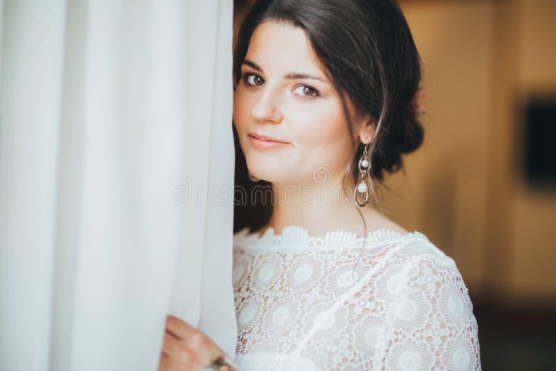 Η όμορφη χαμογελώντας νέα γυναίκα brunette νυφών στο άσπρο φόρεμα δαντελλών κοντά στο παράθυρο, κλείνει επάνω το πορτρέτο στοκ εικόνες