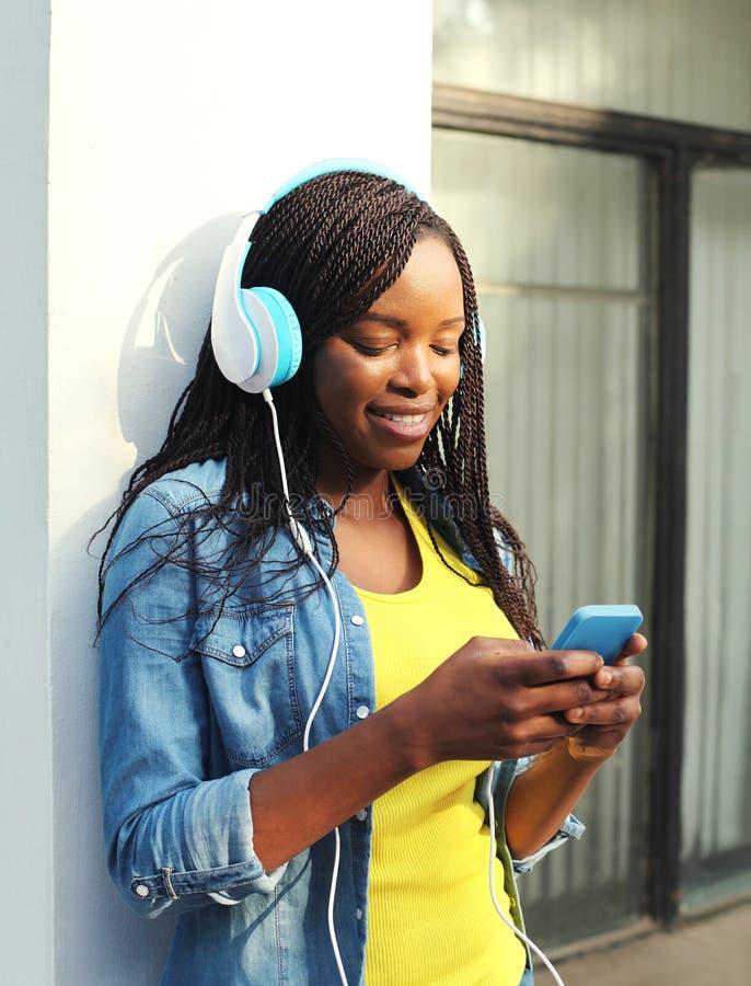 Η όμορφη χαμογελώντας αφρικανική γυναίκα με τα ακουστικά ακούει τη μουσική και χρησιμοποίηση του smartphone στοκ φωτογραφίες