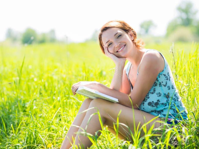Η όμορφη χαμογελώντας γυναίκα διαβάζει το βιβλίο στη φύση στοκ φωτογραφία με δικαίωμα ελεύθερης χρήσης