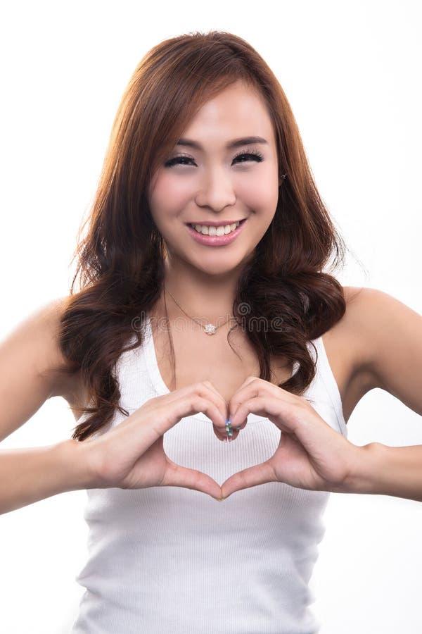 Η όμορφη χαμογελώντας εκμετάλλευση κοριτσιών παραδίδει τη διαμόρφωση μορφής καρδιών στοκ εικόνα