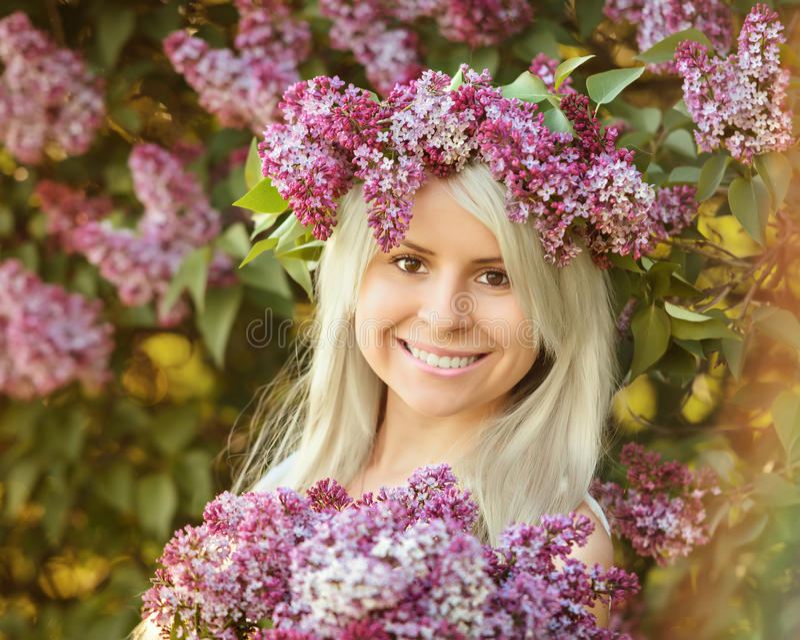 Η όμορφη χαμογελώντας νέα γυναίκα φορά το στεφάνι των ιωδών λουλουδιών στοκ φωτογραφίες