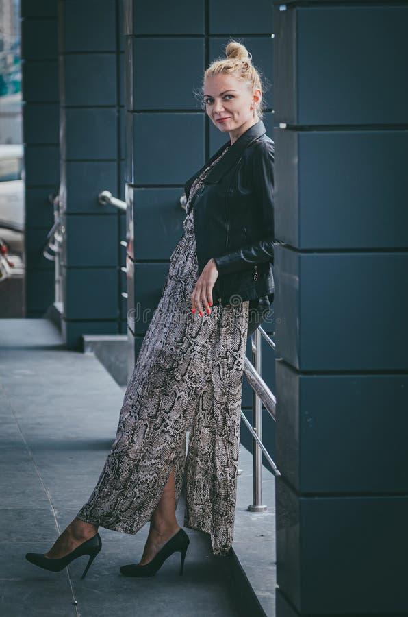 Η όμορφη ψηλή λεπτή γυναίκα ξανθή σε ένα καθιερώνον τη μόδα μακρύ φόρεμα με ένα έρπον φίδι τυπωμένων υλών, σε ένα σακάκι δέρματος στοκ φωτογραφία