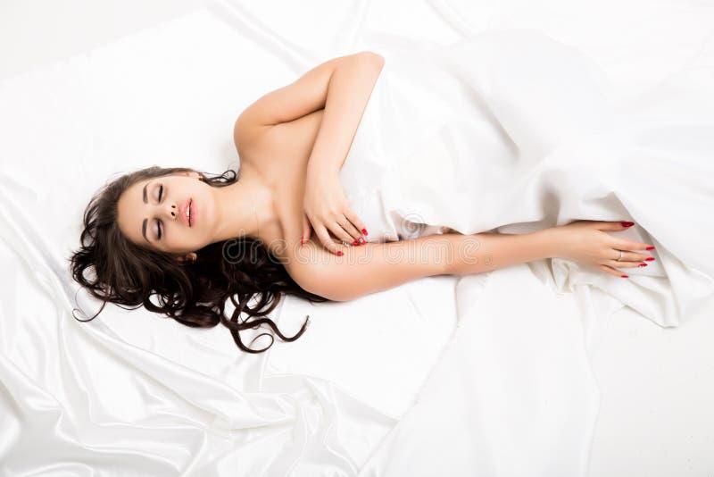 Η όμορφη nude προκλητική κυρία σε κομψό θέτει χαλαρωμένη γυμνή νέα γυναίκα που βρίσκεται σε ένα κρεβάτι κάτω από το άσπρο κάλυμμα στοκ φωτογραφία