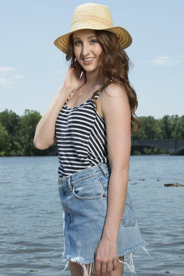 Η όμορφη redhead γυναίκα θέτει κοντά στο νερό στη φούστα τζιν στοκ φωτογραφίες
